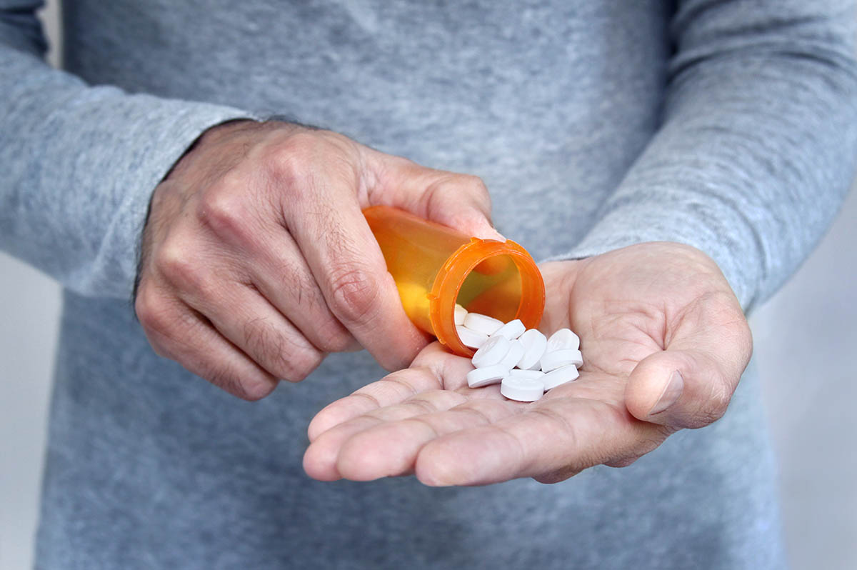 Hands of man holding pill bottle with pills on hand